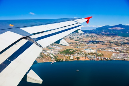 Airplane Wing and city on coastline photo