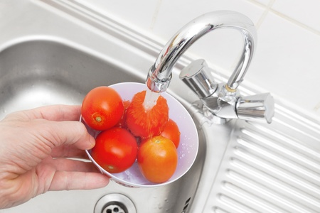 Red tomatoes wash under a water stream photo