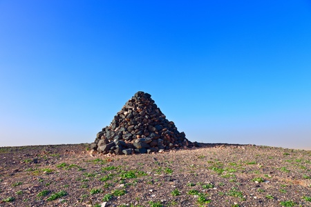 Stone pyramid at mountain peak photo