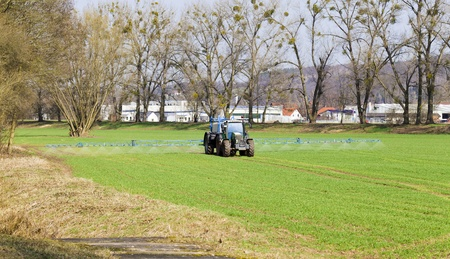 tractor sprayer on green spring field photo