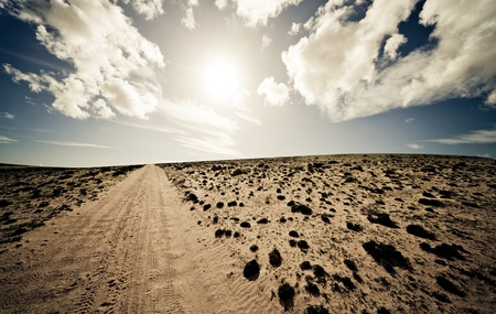 Desert  dirt road and blue sky and Clouds photo