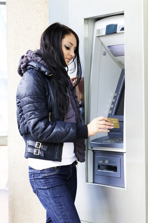The girl draws out money in a cash ATM photo