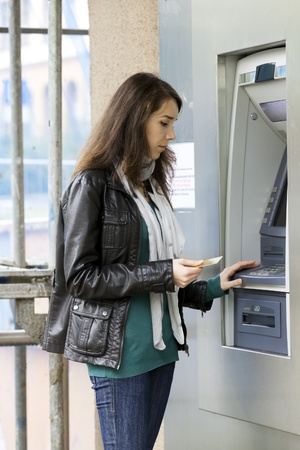 dispense: The girl draws out money in a cash ATM