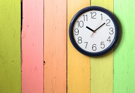 Clock on color wooden plank wall