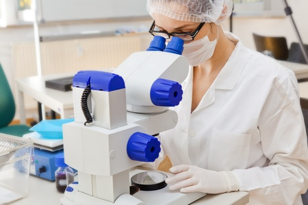 Young woman looking into a microscope Stock Photo - 9347589