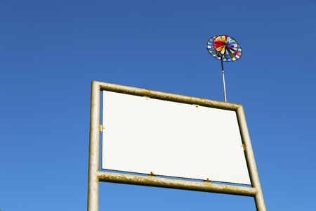 Billboard and toy weathercock on sky background photo
