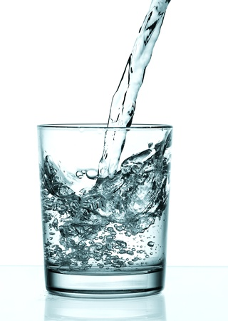 bottled: Drinking water is poured from a bottle into a glass Stock Photo