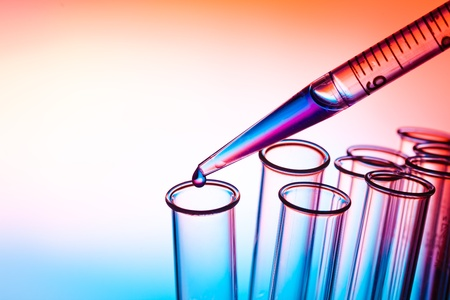 test tube: Pipette adding fluid to one of several test tubes Stock Photo
