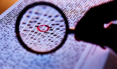 genetica: Mano con una lente d'ingrandimento sulle sequenze di DNA a bande