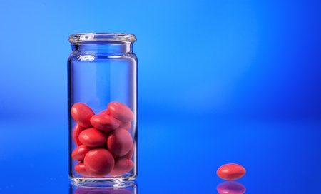 white pills in a glass vial holds the hand Stock Photo - 10348014