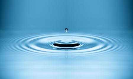 gota: Gota de agua cayendo en agua haciendo un perfecto círculos concéntricos Foto de archivo