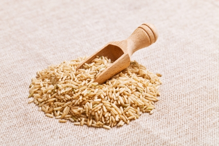 brown rice: Yellow rice in wooden spoon
