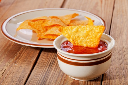 nacho chip: Tortilla chips in dish and salsa sauce  in bowl