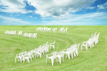 White plastic Chairs on a green grass photo