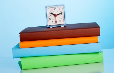 Alarm clock and color books photo