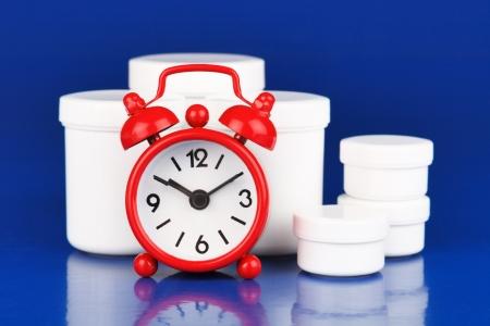 Medications and  small alarm clock photo