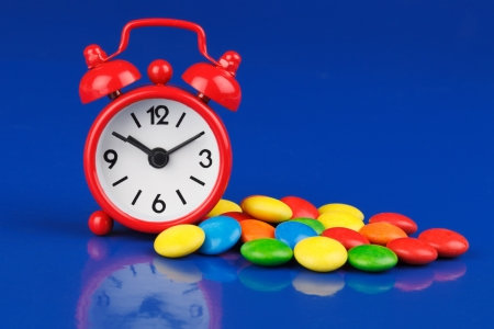 Small red alarm clock and multi-colored candies Stock Photo - 13821485