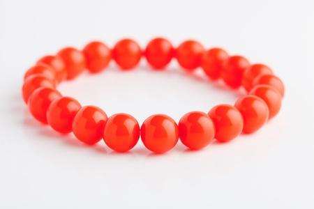 Necklace of orange beads on a white background Stock Photo - 13821475