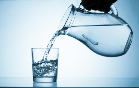tomando agua: Vierta el agua de una jarra en un vaso Foto de archivo