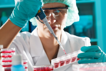 Girl in the microbiology laboratory takes samples pipette