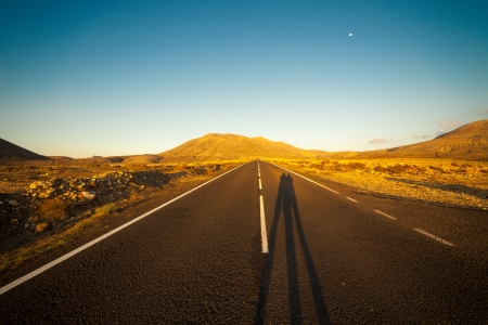 desert highway: Shadow of two people on the highway at sunset and the mountains on the horizon Stock Photo