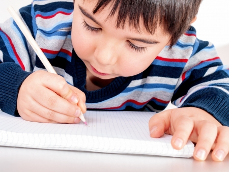 Boy draws a pencil drawing in the notebook photo