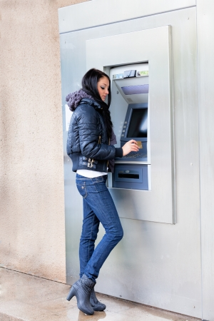 Girl get cash from an ATM on a city street photo