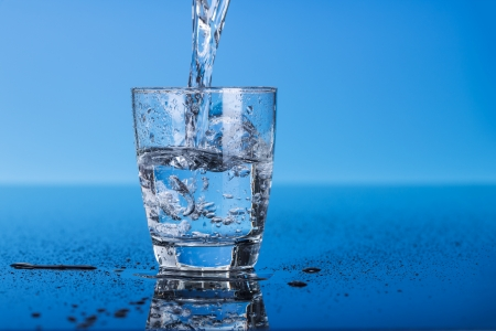 Drinking water is poured into a glass photo