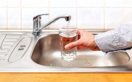rubinetti: Toccare l'acqua potabile che versa nel vetro