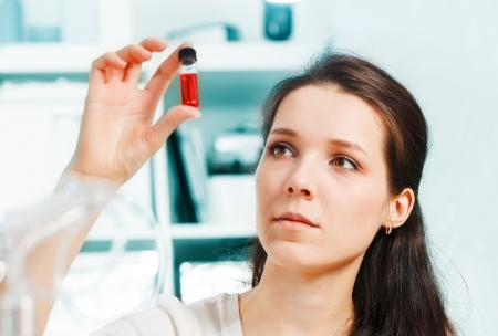 Laboratory assistant with a sample of blood in a test tube photo