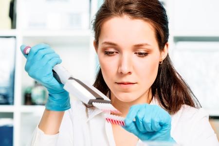 al�rgico: Asistente de laboratorio con una muestra de sangre en un tubo de ensayo