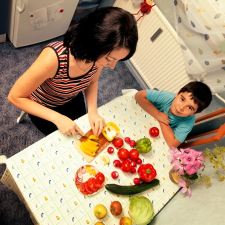 furniture store: Mother and child son cut vegetables for a meal food in the kitchen