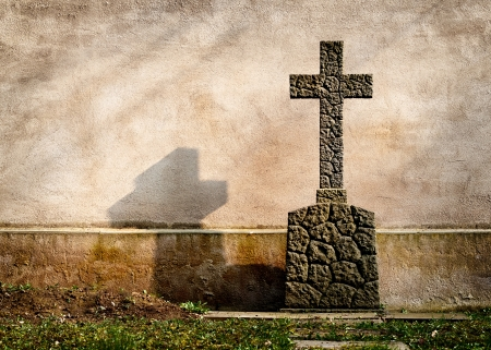 memorial cross: Cruz en una tumba en el fondo de una pared oscura