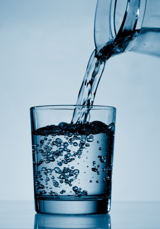 quality home: Drinking water is poured from a jug into a glass Stock Photo
