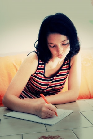 woman writes a letter to on paper photo