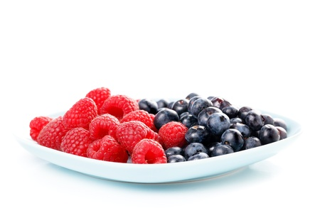 Red raspberry and black bilberry in  plate, isolated on white photo