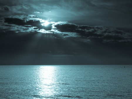 over the sea: moon in the night sky over the sea