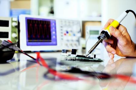 circuito electronico: las partes electr�nicas de soldadura en una placa de circuito impreso Foto de archivo
