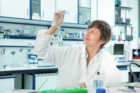 biopsia: Laboratorio asistente de explorar las secciones de tejido celular. biopsia