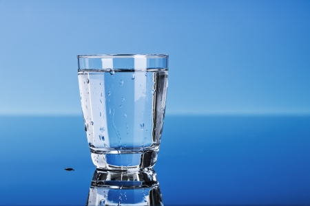 drinking water in a glass on blue  photo