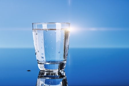 glass of drinking water on a blue table Stock Photo