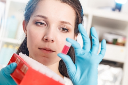 Girl with a chemical sample in a forensic laboratory photo
