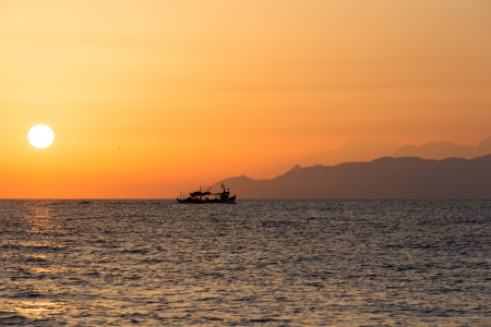 Sunset sky in the Aegean sea with boat and mountains, Santorini photo