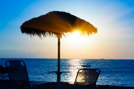 Beach umbrella on the beach at sunset, Santorini Greece photo