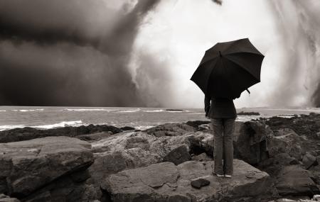 winter storm: girl with umbrella on the ocean shore, melancholia concept