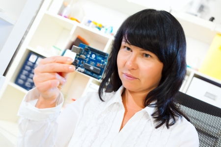 woman worker checks the printed circuit board microcontroller photo