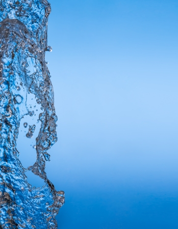 existence: clean water splash on blue background. Water is a necessary condition for the existence of life on earth