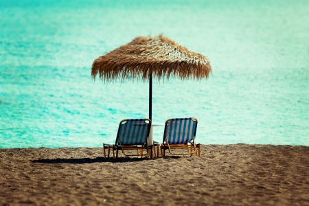 beach sun beds and straw umbrella on the beach photo