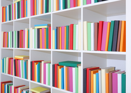 Books on a white shelf, stack of colorful books in Library photo