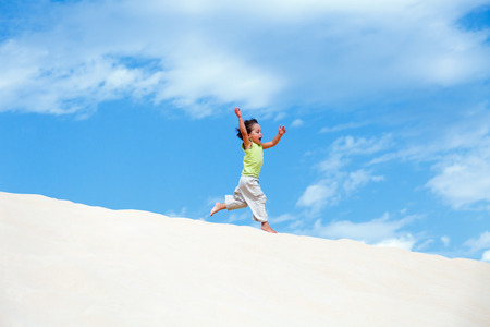 little boy running on sand dune photo